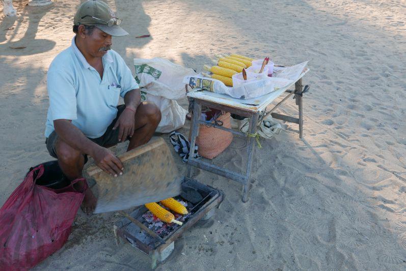 Der Mann verkauft leckeren gebutterten und gegrillten Mais