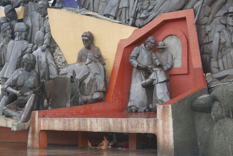 Eine Mutter mit ihrem nackten Kind unter einem Denkmal - Armut begegnete uns leider sehr häufig in Manila