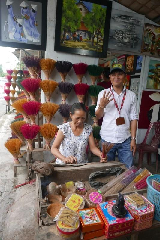Die Frau stellt die Räucherstäbchen her, neben ihr steht unser Guide